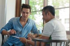 Deux hommes à l'aide de la Tablette, types asiatiques d'amis de course de mélange Photographie stock