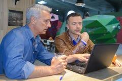Deux hommes à l'aide de l'ordinateur portable dans la barre de café Images libres de droits