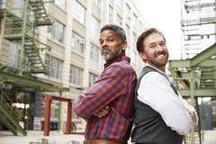 Deux hommes âgés par milieu reculent pour soutenir le lieu de travail extérieur image libre de droits