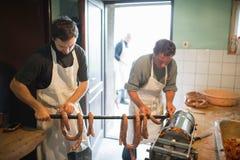 Deux hommes accrochant les saucisses crues faites maison sur le bâton en bois Image stock