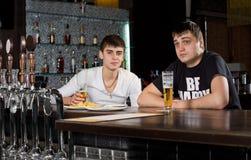 Deux hommes adolescents buvant au bar Images libres de droits