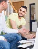 Deux hommes adultes avec l'ordinateur portable à l'intérieur Photos libres de droits