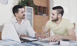Deux hommes adultes avec l'ordinateur portable à l'intérieur Photographie stock libre de droits