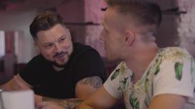 Deux hommes adultes font tinter des verres au compteur de barre souriant et parlant Amis masculins décontractés refroidissant ens banque de vidéos