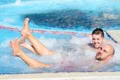 Deux hommes appréciant le bain moussant de baquet chaud de jacuzzi extérieur Image libre de droits