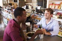 Deux hommes appréciant le déjeuner dans le restaurant d'épicerie fine Images stock