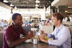 Deux hommes appréciant le déjeuner dans le restaurant d'épicerie fine photos stock