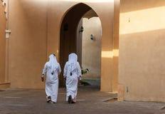 Deux hommes arabes non identifiables dans l'habillement blanc de thobe marchant loin images libres de droits