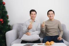 Deux hommes asiatiques utilisant le chandail tenant le verre à la maison du de champagne Photographie stock