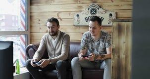 Deux hommes attirants tenant le contrôleur de jeu jouant des jeux vidéo banque de vidéos