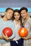 Deux hommes avec des billes et fille dans le bowling matraquent Images libres de droits