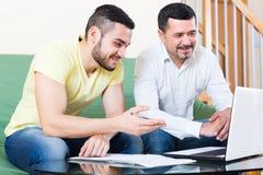 Deux hommes avec l'ordinateur portable à la maison Photographie stock libre de droits