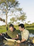 Deux hommes avec la carte contre le lac Photographie stock libre de droits