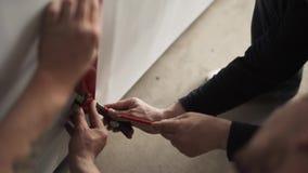 Deux hommes avec la ligne d'aspiration de coupe-papier de crayon et sur la feuille blanche et la couper clips vidéos