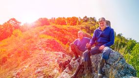 Deux hommes avec les b?tons scandinaves en haut de la montagne et d'admirer la vue du taiga d'Ural d'en haut image libre de droits