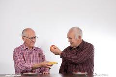 Deux hommes avec les fruits, la pomme et la banane images libres de droits