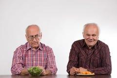 Deux hommes avec sain et la nourriture industrielle photographie stock