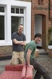 Deux hommes avec Sofa Outside House Photo stock