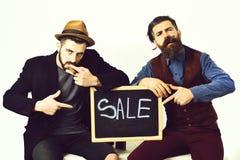 Deux hommes barbus, hippies élégants caucasiens avec la moustache, inscription de vente images stock
