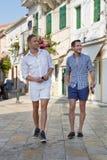 Deux hommes beaux marchant par la ville. Images stock