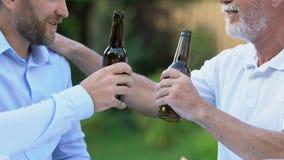 Deux hommes buvant la bière, des traditions durables de brassage, plus loin et parler de fils banque de vidéos