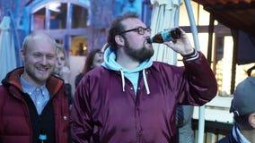 Deux hommes caucasiens mûrs portant les vêtements sport ont la conversation tenant la bière clips vidéos