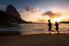 Deux hommes courant dans la plage Photo stock
