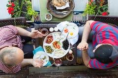 Deux hommes dénominatifs multi priant au-dessus de la nourriture Photographie stock