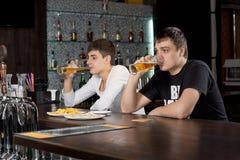 Deux hommes détendant à la bière potable de barre Photographie stock