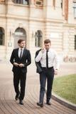 Deux hommes d'affaires élégants parlant et souriant dehors Photos libres de droits