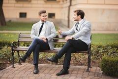 Deux hommes d'affaires élégants parlant et souriant dehors Images stock