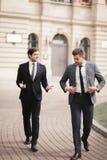 Deux hommes d'affaires élégants parlant et souriant dehors Photo stock
