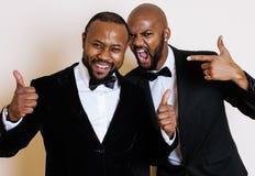 Deux hommes d'affaires afro-américains dans les costumes noirs pose émotive, faisant des gestes, souriant noeuds papillon de port Images libres de droits