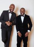 Deux hommes d'affaires afro-américains dans les costumes noirs pose émotive, faisant des gestes, souriant noeuds papillon de port Photographie stock