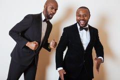 Deux hommes d'affaires afro-américains dans les costumes noirs pose émotive, faisant des gestes, souriant noeuds papillon de port Photos stock