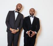 Deux hommes d'affaires afro-américains dans les costumes noirs pose émotive, faisant des gestes, souriant noeuds papillon de port Images stock