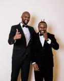 Deux hommes d'affaires afro-américains dans les costumes noirs pose émotive, faisant des gestes, souriant noeuds papillon de port Photo stock