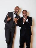 Deux hommes d'affaires afro-américains dans les costumes noirs pose émotive, faisant des gestes, souriant noeuds papillon de port Photo libre de droits