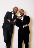 Deux hommes d'affaires afro-américains dans les costumes noirs pose émotive, faisant des gestes, souriant noeuds papillon de port Photos libres de droits
