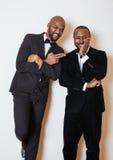 Deux hommes d'affaires afro-américains dans les costumes noirs pose émotive, faisant des gestes, souriant noeuds papillon de port Image libre de droits