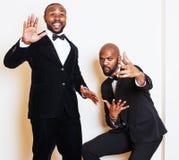Deux hommes d'affaires afro-américains dans les costumes noirs pose émotive, faisant des gestes, souriant noeuds papillon de port Image stock