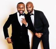 Deux hommes d'affaires afro-américains dans les costumes noirs pose émotive, faisant des gestes, souriant noeuds papillon de port Photographie stock libre de droits