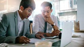 Deux hommes d'affaires analysant quelques écritures au café images stock