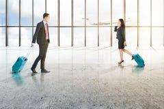 Deux hommes d'affaires asiatiques attirants avec le téléphone portable et les valises bleues marchant sur le hall d'aéroport photos stock