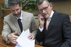 Deux hommes d'affaires avec des écritures à un restaurant Photo libre de droits