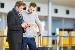 Deux hommes d'affaires avec le comprimé dans le terminal d'aéroport photos stock