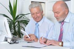 Deux hommes d'affaires avec un ordinateur portable Photo stock