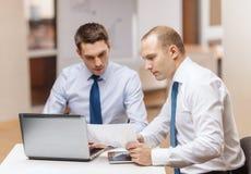 Deux hommes d'affaires ayant la discussion dans le bureau Image stock