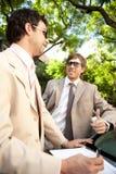 Hommes d'affaires se réunissant autour de la voiture. Image libre de droits