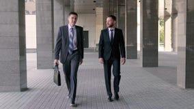 Deux hommes d'affaires beaux causant ensemble comme ils marchent le long de l'immeuble de bureaux banque de vidéos